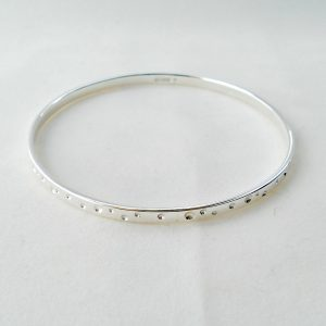 Silver bangle with circle pattern